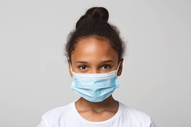 Porträt des kleinen schwarzen Mädchens trägt medizinische Maske – Foto