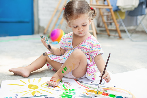 1042756824 istock photo Portrait of little blonde girl painting, summer outdoor. 1037812314