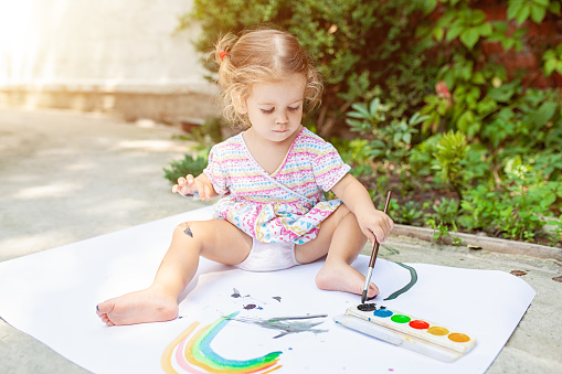 1042756824 istock photo Portrait of little blonde girl painting, summer outdoor. 1037812318