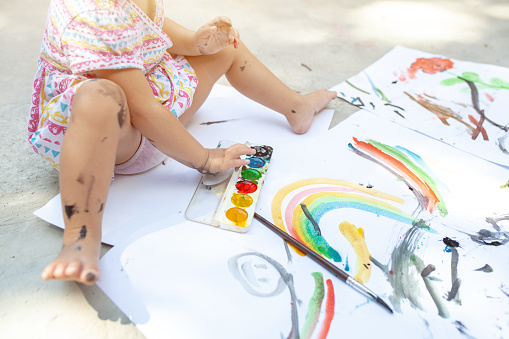 1042756824 istock photo Portrait of little blonde girl painting, summer outdoor. 1042756812