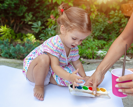 1042756824 istock photo Portrait of little blonde girl painting, summer outdoor. 1042756816
