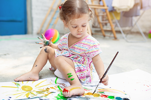 1042756824 istock photo Portrait of little blonde girl painting, summer outdoor. 1046786924
