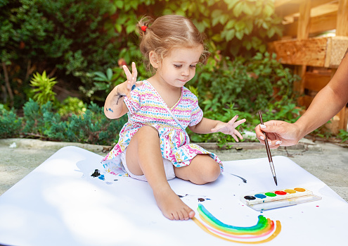 1042756824 istock photo Portrait of little blonde girl painting, summer outdoor. 1046786928