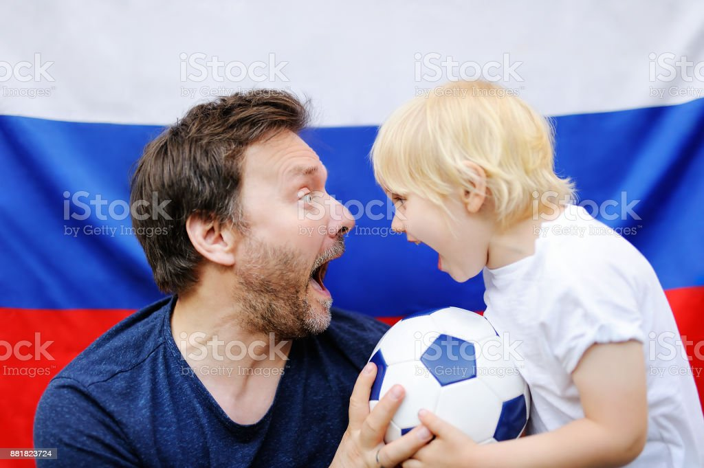 Portrait of little boy and his middle age father with russian flag on background stock photo