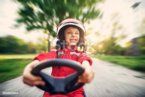 Little boy driving fast a go kart. The cute boy is aged 6 and is making funny face.