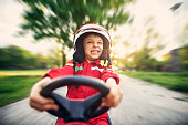 Little boy driving fast a go kart. The cute boy is aged 6 and is making funny face.\n