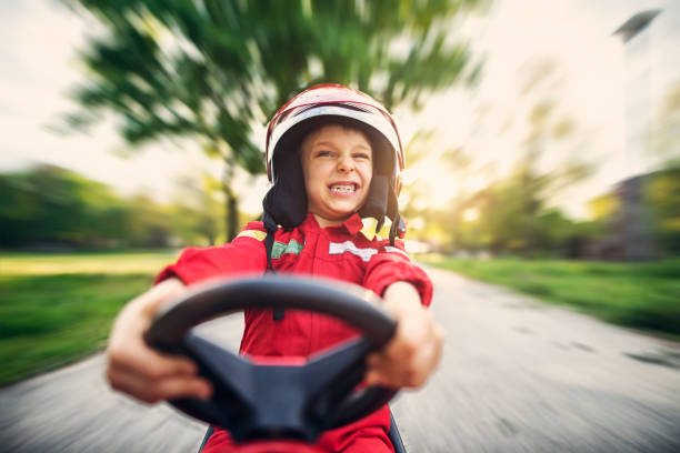 Portrait of little boy driving fast his toy car Little boy driving fast a go kart. The cute boy is aged 6 and is making funny face.  clenching teeth stock pictures, royalty-free photos & images