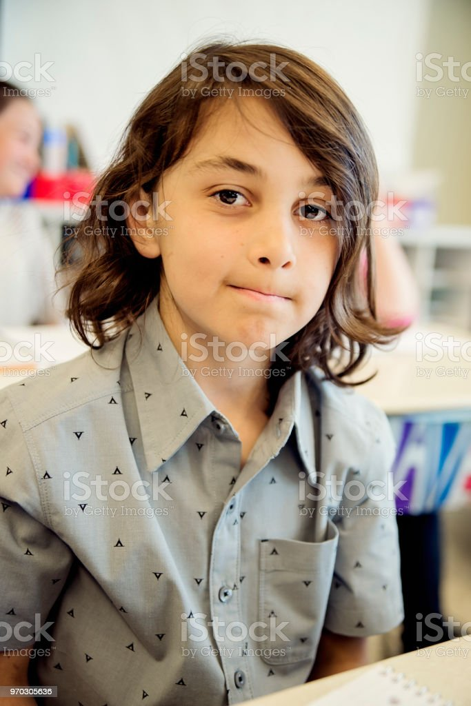 Portrait of little boy in classroom, sitting at his desk. royalty-free stock photo