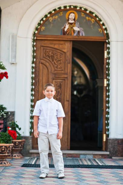 白い服と弓ネクタイに小さな男の子の肖像最初の神聖な交わりの背景チャーチゲート - 独身の若者 ストックフォトと画像