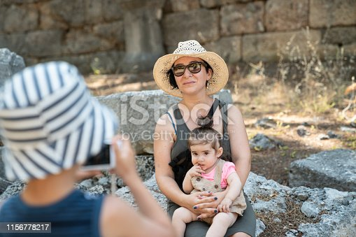 Portrait of 6 years boy photographing his family in outdoor. Mother is holding baby daughter while son is holding a camera for photographing. They are seen in antique ruins. Mother and son wearing sun hats. Shot in outdoor daylight with a full frame mirrorless camera.