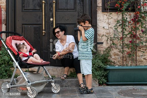 Portrait of 6 years boy photographing his family in outdoor. Mother is holding baby daughter while son is holding a camera for photographing. Shot in outdoor daylight with a full frame mirrorless camera.