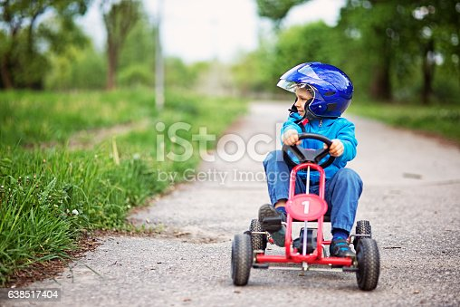 Little boy aged 6 driving a pedal go-kart, kart, soapbox car or cyclekart. Little boy is smiling and enjoying the spring ride.