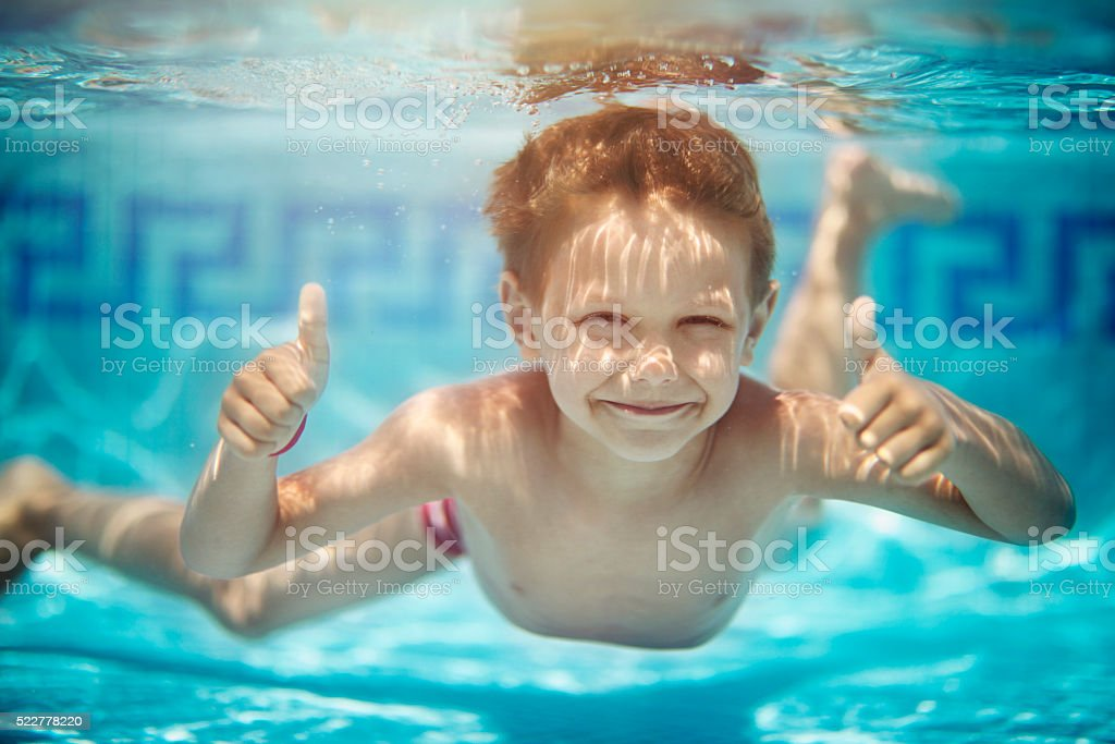 Portrait of little boy swimming underwater in pool stock photo