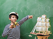 Portrait of little boy wearing a striped sailors shirt and hat holding binoculars and pointing forward. A toy ship model is seen next to him. He is seen in front of green chalkboard. Cloud and sky sketch is seen on blackboard. Shot indoor with a medium format camera.