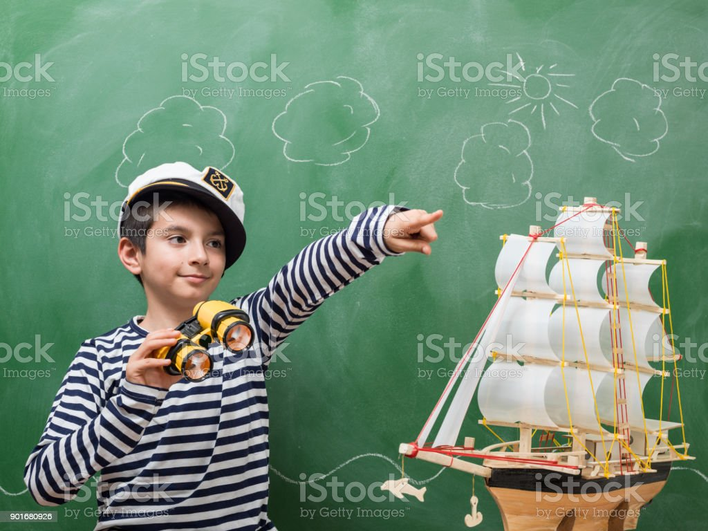 Portrait Of Little Boy Wearing Striped Sailors Shirt And Hat stock photo