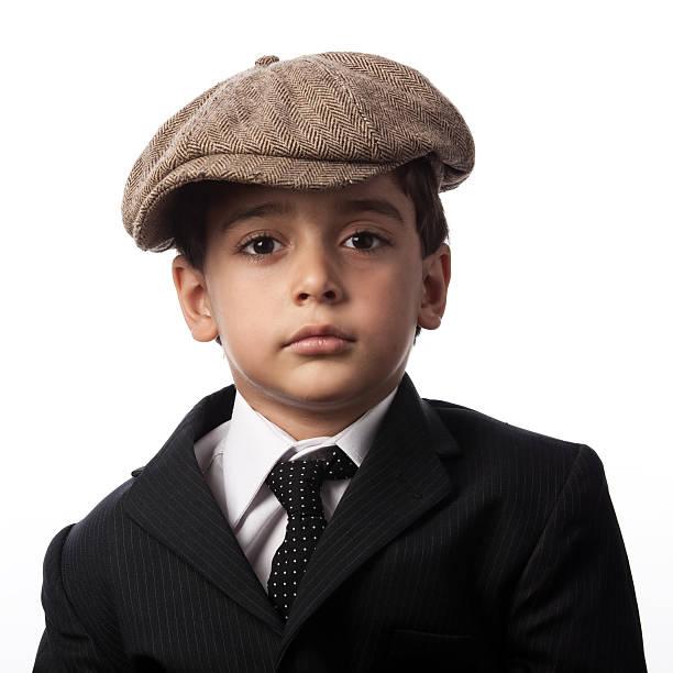 porträt der kleine junge mit gestreiften anzug und flat cap - schiebermütze stock-fotos und bilder