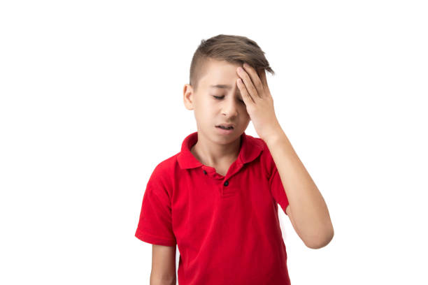 Portrait of little boy with headache over white background stock photo