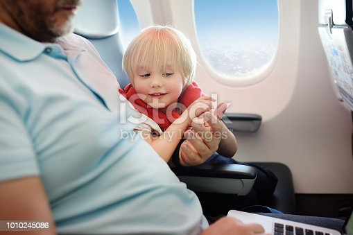 istock Portrait of little boy with his father during traveling by an airplane 1010245086