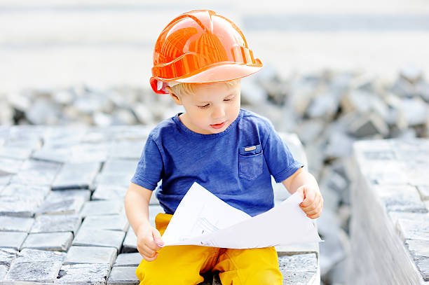 Portrait Of Little Builder In Hardhats Reading Construction Drawing Stock Photo