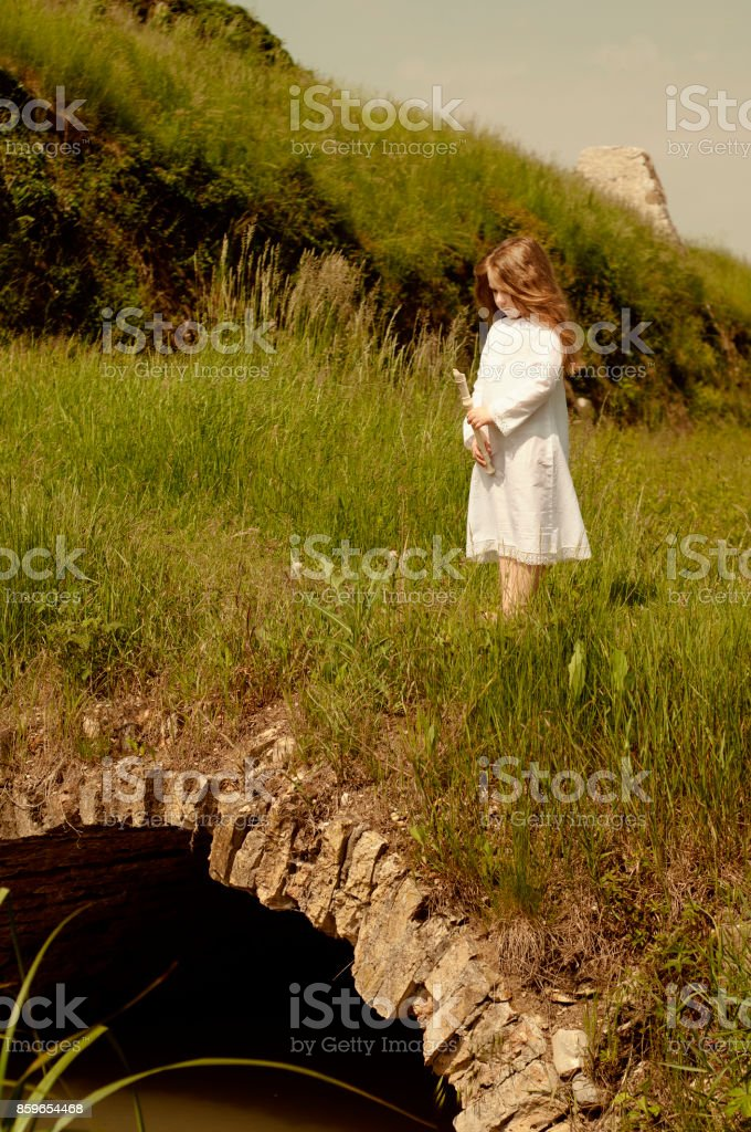 Portrait of little Caucasian girl in white dress with flute stock photo