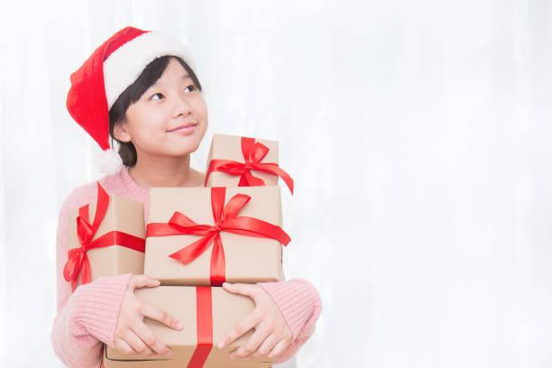 赤い帽子をかぶった小さな可愛いアジアの女の子の肖像画は、コピースペース、クリスマスボクシングデーのコンセプトで見上げる贈り物の箱を保持しています ストックフォト