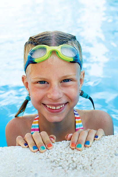 Portrait of little cute girl in the swimming pool. Sportime stock photo