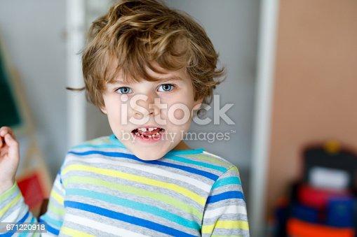 933458532 istock photo Portrait of little cute school kid boy colorful school uniform fashion clothes. 671220918