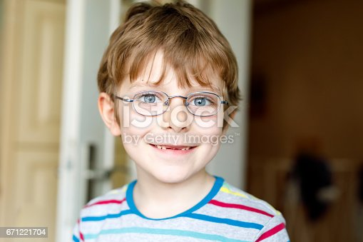 933458532 istock photo Portrait of little cute school kid boy with glasses 671221704