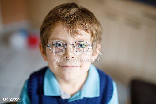 933458532 istock photo Portrait of little cute school kid boy with glasses 680402202