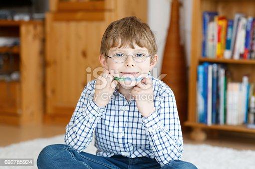 933458532 istock photo Portrait of little cute school kid boy with glasses 692785924