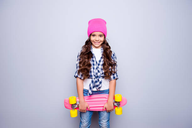 Portrait of little cute smiling girl with pink skate-board in pink hat who is ready to ride on the street standing over grey background Portrait of little cute smiling girl with pink skate-board in pink hat who is ready to ride on the street standing over grey background pre adolescent child stock pictures, royalty-free photos & images