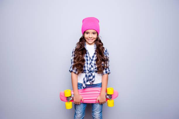 porträt der kleine süße lächelndes mädchen mit rosa skate-board in rosa hut, das bereit ist, auf der straße stehend über grauen hintergrund zu fahren - kind vor der pubertät stock-fotos und bilder