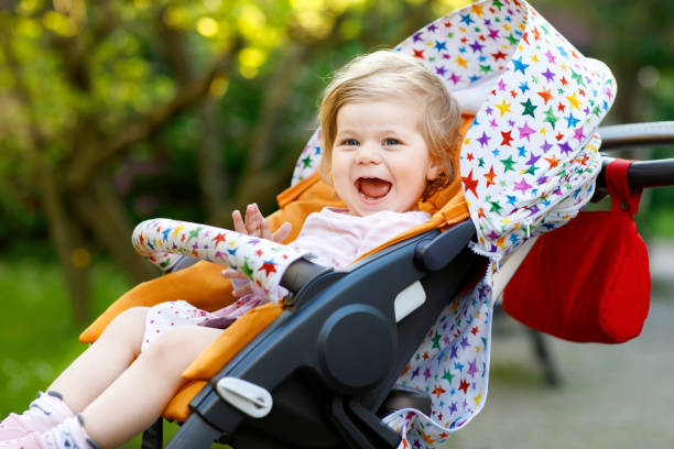 Portrait of little cute toddler girl sitting in stroller or pram and going for a walk. Happy cute baby child having fun outdoors Portrait of little cute toddler girl sitting in stroller or pram and going for a walk. Happy cute baby child having fun outdoors. Healthy daughter. baby stroller stock pictures, royalty-free photos & images