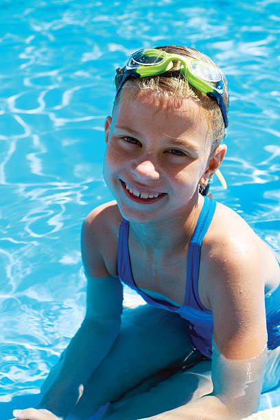 portrait of little girl by the side of the pool. stock photo