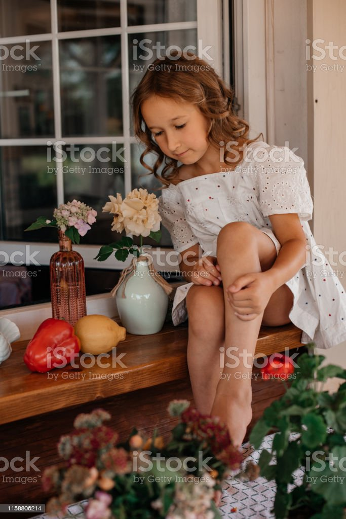 Little girl with kind eyes is sitting by the white window and hug...
