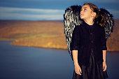 Portrait of little girl dressed like a black angel