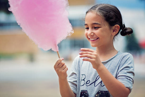 Portrait of little girl eating cotton candy stock photo