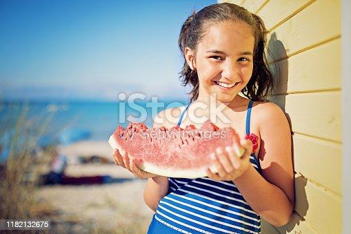 Portrait of little girl eating watermelon on the beach