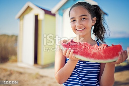 Portrait of little girl eating watermelon on the beach