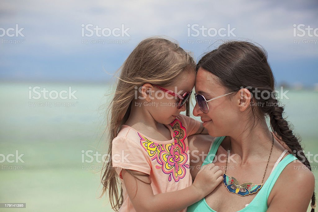 Portrait of little girl hugging with her mother on beach royalty-free stock photo