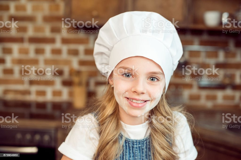 Portrait Of Little Girl In Chef Hat And Flour On Face Stock