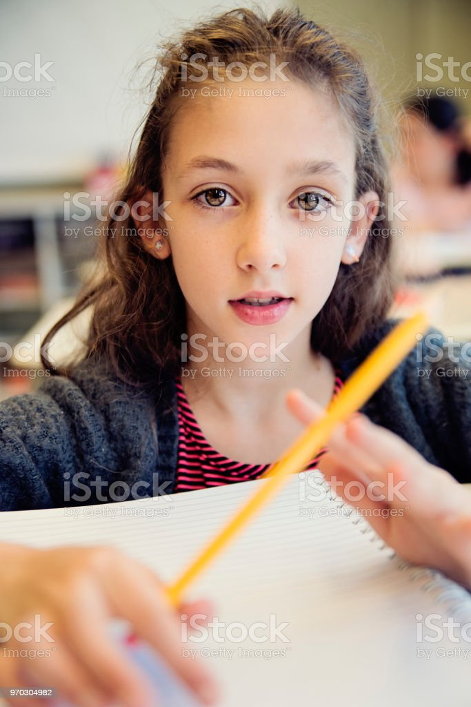 Portrait of little girl in classroom, sitting at her desk. royalty-free stock photo