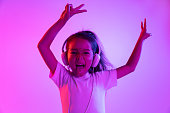 Beautiful female half-length portrait isolated on purple backgroud in neon light. Young emotional teen girl in eyeglasses. Human emotions, facial expression concept. Trendy colors. Dancing, smiling.