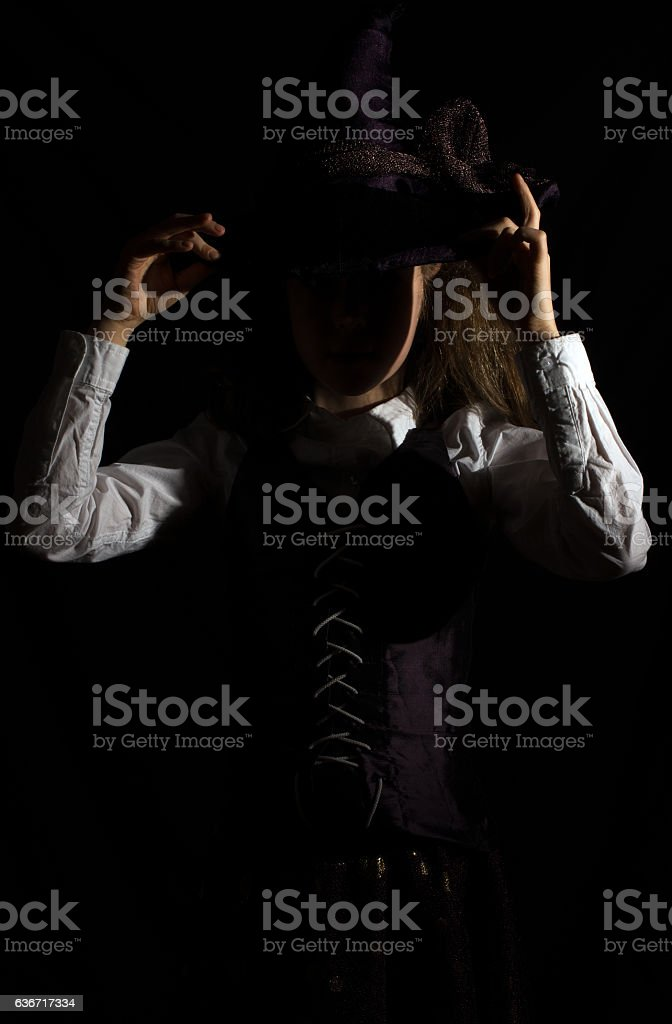 Portrait of little girl in witch costume. Incognito. stock photo