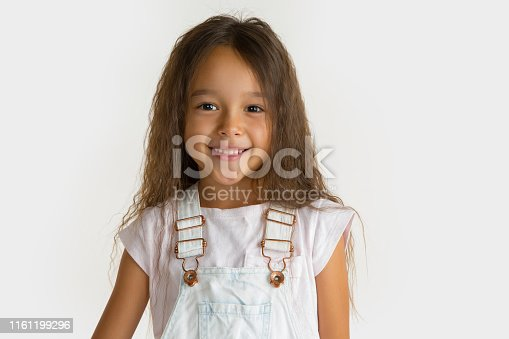 Beautiful female half-length portrait isolated on white studio background. Little emotional asian girl wearing white. Facial expression, human emotions, advertising concept. Smiling, confusing.