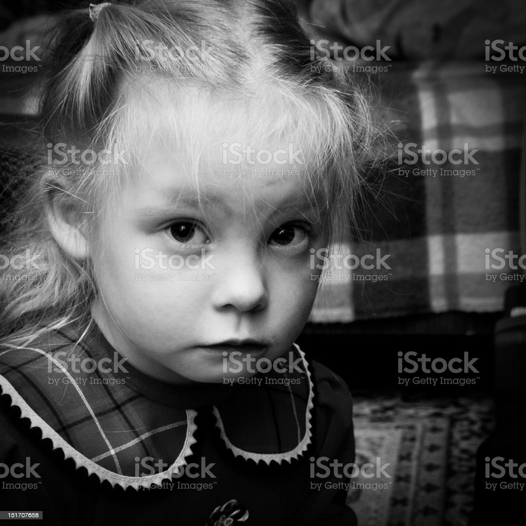 Portrait of little girl looking into camera Close-up portrait of little blond upset girl looking into camera. Black and white grainy image imitating film effect. Beautiful People Stock Photo