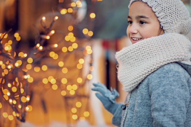 Portrait of little girl looking store window at Christmas stock photo