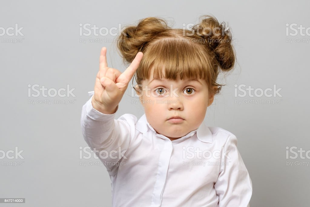Portrait of little girl making rock and roll sign isolated stock photo