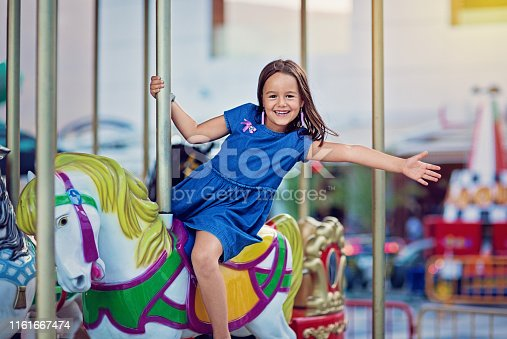 Happy girl is riding horse on carousel