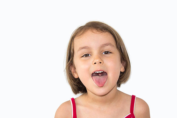 portrait of little girl sticking out toungue on white background - sticking out tongue stock photos and pictures